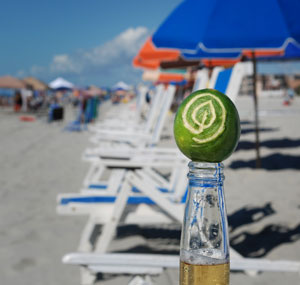 GGW logo carved into a lime sitting on a Corona beer with beach chair in the background