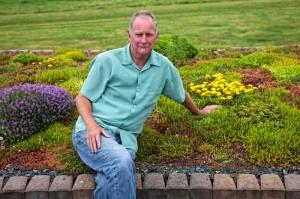 Ed Snodgrass sitting amongst beautiful rooftop garden plants